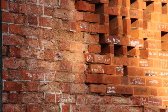 Một vài viên gạch đã bong tróc, tường bôi bẩn đầy vết các ký tự. Ảnh: Lê Phong