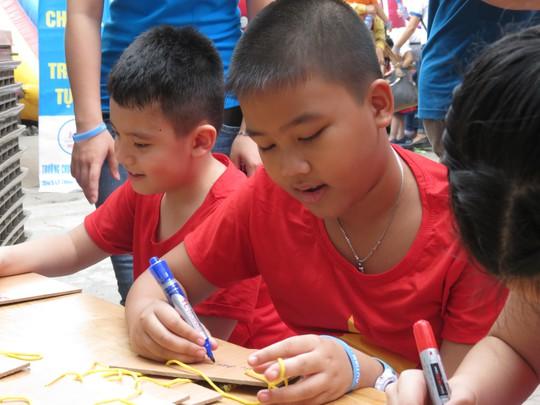Khuôn mặt cậu bé ánh lên nét hạnh phúc và tin tưởng khi viết điều ước lên tấm gỗ.