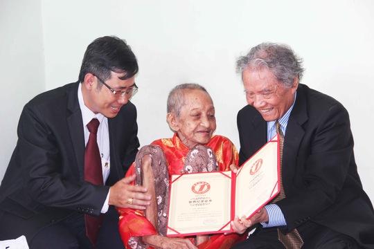 Đại diện Tổ chức Kỷ lục Việt Nam trao bằng công nhận Kỷ lục Cụ bà thọ nhất thế giới của Hiệp hội Kỷ lục Thế giới cho cụ Nguyễn Thị Trù vào sáng 9-5 (ảnh do Vietkings cung cấp)