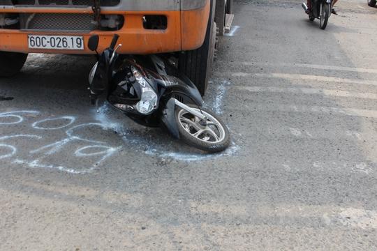 Xe máy của người phụ nữ bị cuốn vào gầm trước xe.