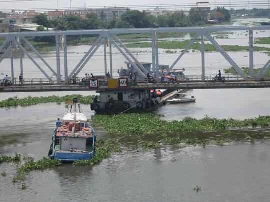 Chiếc sà lan cố chui qua cầu Bình Lợi khi mực nước dâng cao khiến phần đuôi bị kẹt lại rồi đội ngược gầm cầu