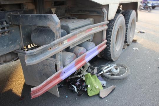 Xe máy của nạn nhân vỡ nát mắc kẹt dưới bánh xe ben
