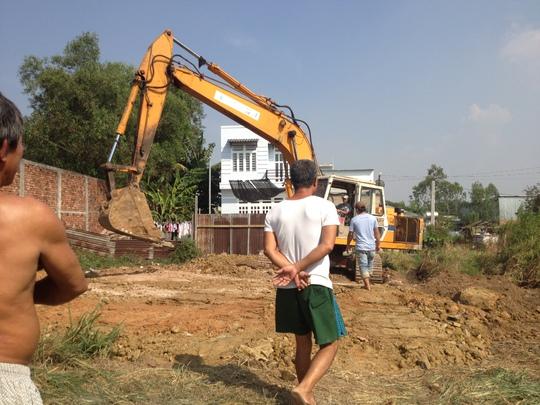 Máy xúc của công ty Đồng Xanh đào hố chôn nước thải bị người dân giữ lại