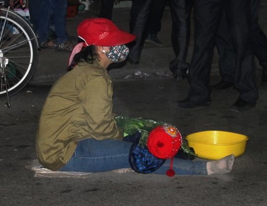 Người mẹ ngồi đợi chờ lòng thương của người qua lại, trong khi đó đứa con thì nằm sõng soài trong cái lạnh và mưa phùn