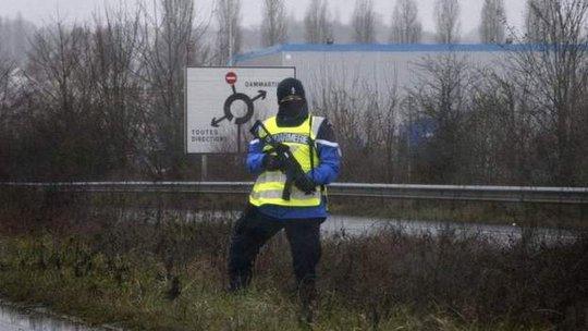 Cảnh sát canh gác trên ở tuyến đường dẫn vào tòa nhà nghi phạm đang bắt giữ con tin ở Dammartin-en-Goële. Ảnh: BBC