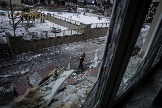A Ukrainian man walks through the debris produced after the Ukrainian Army hit a building in Voroshilovsky area, center of Donetsk, Ukraine. Sunday, Jan. 18,...