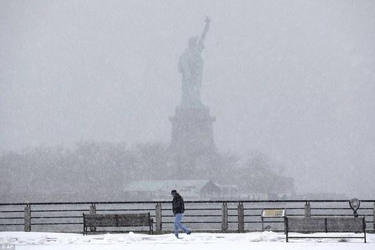 Một người đàn ông đi lững thững trước Tượng nữ thần tự do trong bão tuyết. Ảnh: AP
