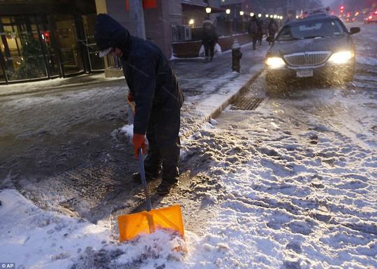 Một người đàn ông xúc tuyết trên con phố ở Brooklyn. Ảnh: AP