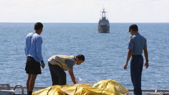 Crew members inspect bags containing bodies believed to be victims of AirAsia Flight 8501 on the deck of Indonesian Navy ship KRI Banda Aceh, on the Java Sea, Indonesia, Friday, Jan. 23, 2015.