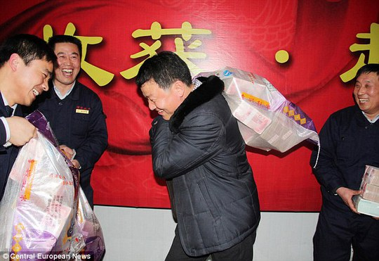 In the money: Workers in communist China are handed sackfuls of bonus money, some containing what would be several years worth of salary for westerners