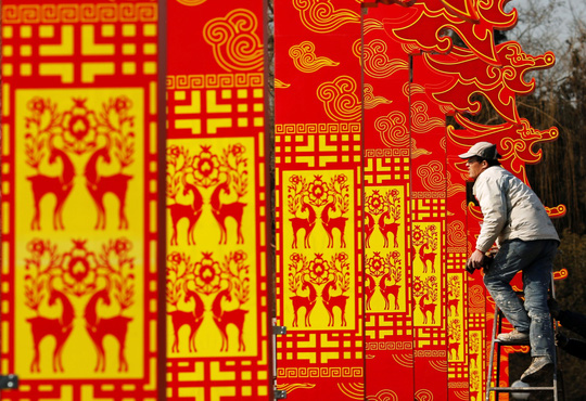 A man installs decorations for the upcoming Chinese Lunar New Year celebrations at Taoranting park in Beijing February 9, 2015. Photo by Kim Kyung-Hoon/REUTERS.