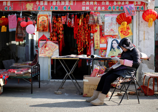A vendor, selling traditional decorations for the upcoming Chinese Lunar New Year, reads a newspaper as she waits for customers at a migrant workers village in Beijing February 12, 2015. Photo by Kim Kyung-Hoon/REUTERS.