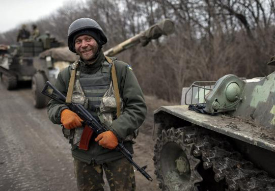 A member of the Ukrainian armed forces and armoured personnel carriers smiles as they prepare to move to pull back from Debaltseve region, near Artemivsk February 26, 2015.  REUTERS-Gleb Garanich