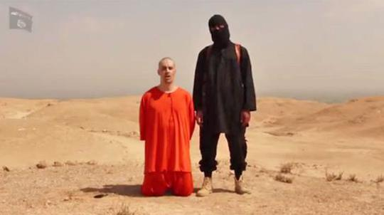 James Foley kneeling beside an Islamic State militant in the video.