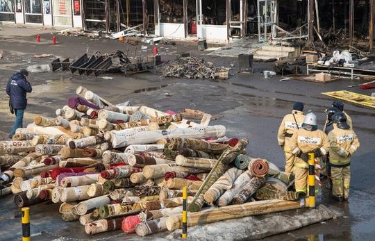 Спасатели во время разборов у сгоревшего торгового центра.