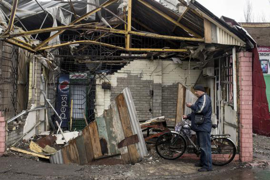 A man checks his mobile phone in front of his destroyed house in the town of Debaltseve, north-east from Donetsk, March 13, 2015. REUTERS-Marko Djurica