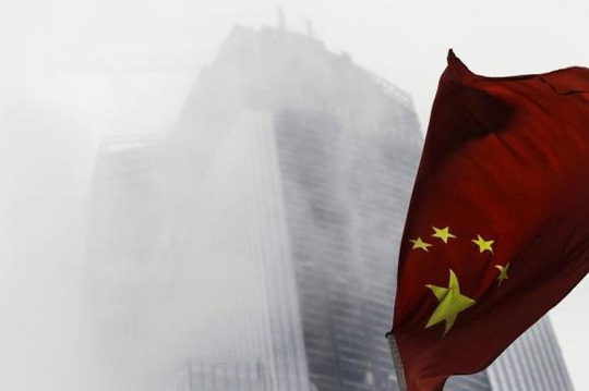 A Chinese national flag flutters in front of a construction site in Guangzhou, Guangdong province, November 7, 2014. EUTERS/Alex Lee
