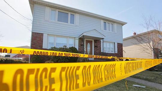 Police tape marks off a home where the bodies of an elderly couple were found Monday, Apr
