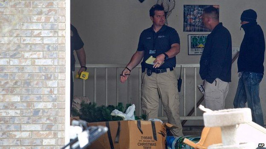 Authorities investigate a crime scene where seven infant bodies were discovered and packaged in separate containers at a home in Pleasant Grove, Utah 14 April 2014