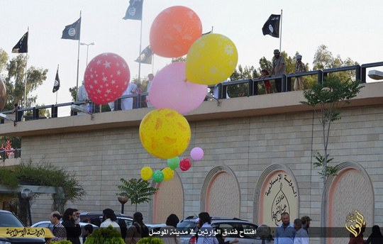 Party time: ISIS chilling black and white banners are seen fluttering in the wind while an array of brightly-coloured balloons are released into the air in celebration at the hotels reopening