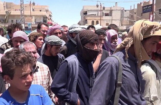 Crowd: Hundreds of men and young boys watch on (pictured) as the men are mutilated in a public square, supposedly in the Syrian city of Homs