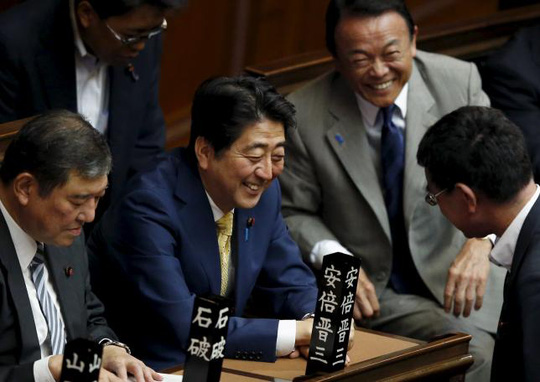 Japans Prime Minister Shinzo Abe (C) smiles with Finance Minister and Deputy Prime Minister Taro Aso (2nd R) and other lawmakers before the lower house plenary session at the parliament in Tokyo July 16, 2015. REUTERS/Toru Hanai