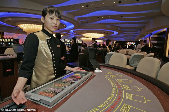 A croupier poses at the opening of the Sands Casino in Macau in 2005. The Chinese government has become concerned by the amount of money gambled away by its own officials on trips to the city