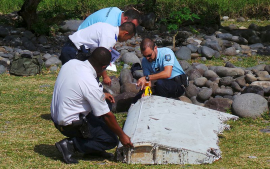 French gendarmes and police inspect a large piece of plane debris which was found on the beach in Saint-Andre, on the French Indian Ocean island of La Reunion, July 29, 2015. Frances BEA air crash investigation agency said it was examining the debris, in coordination with Malaysian and Australian authorities, to determine whether it came from Malaysia Airlines Flight MH370, which vanished last year in one of the biggest mysteries in aviation history. Picture taken July 29, 2015. REUTERS/Zinfos974/Prisca Bigot TPX IMAGES OF THE DAY - RTX1MCP2
