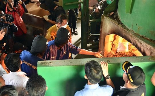 Các nghi phạm đeo mặt nạ đốt số ma túy.Ảnh: SCMP