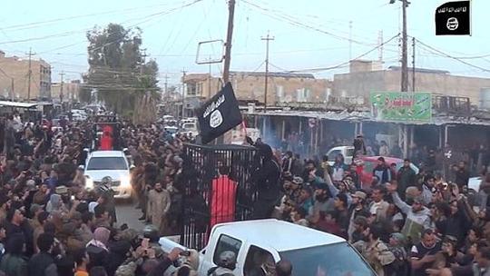 Tù binh người Kurd bị IS đóng cũi diễu hành ngoài đường. Ảnh: News.com.au