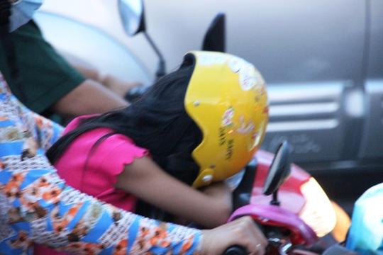 Trẻ em mệt mỏi nằm gục trên xe trong lúc kẹt xe