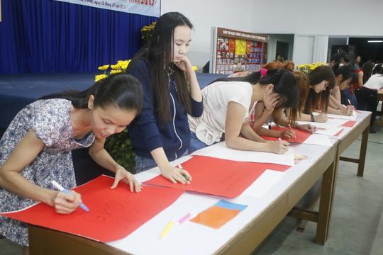 Nữ công nhân Công ty Huê Phong hào hứng tham gia thi viết câu chúc Xuân trên giấy