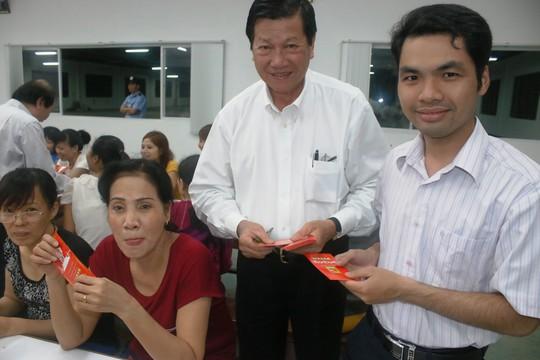 Ông Sy Sâm Cau (giữa), Phó Chủ tịch HĐQT Công ty Huê Phong lì xí Tết cho công nhân