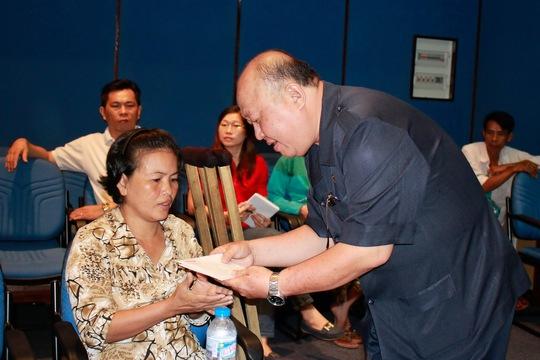 Ông Võ Văn Đặng, Phó Bí thư Thường trực Đảng ủy Ngân hàng Sacombank, trao tiền hỗ trợ cho công nhân  ảnh: HOÀNG TRIỀU