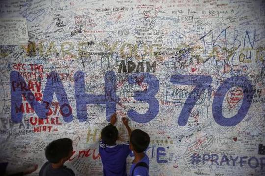 Trẻ em viết các thông điệp hy vọng cho máy bay MH370 bên ngoài sân bay quốc tế Kualum Lumpur hôm 14-6. Ảnh: Reuters