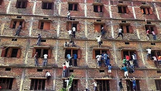Phụ huynh trèo tường ném phao cho con em đang làm bài thi bên trong. Ảnh:PRESS TRUST OF INDIA