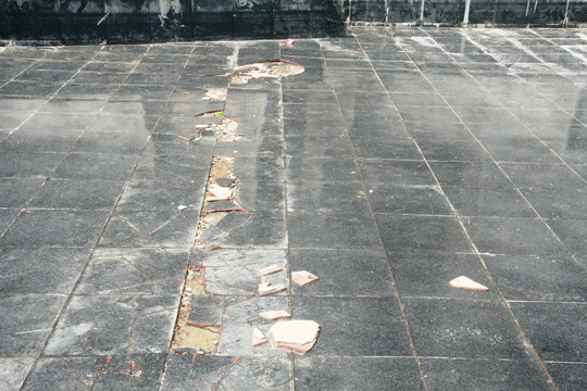 Gạch bị bong tróc một đường dài phía dưới chân tượng đài