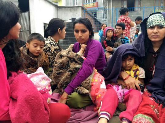 Các bà mẹ ôm con ngồi ngoài đường ở Kathmandu. Ảnh: Reuters