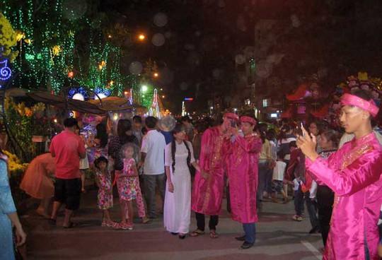 Các bạn trẻ diện áo dài dân tộc để chụp hình ở đường hoa Tây Đô. Ảnh: Phạm Công