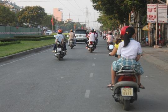 Nhiều học sinh vẫn không đội mũ bảo hiểm khi được cha mẹ chở đi học trên đường Trần Não (quận 2)