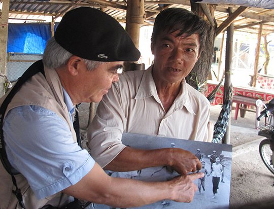 Nhà báo Nick Út và ông Hồ Văn Bôn đang chỉ vào hình ảnh ông Bôn khi chỉ mới là một cậu bé trong bức ảnh. Ảnh: T. Hằng