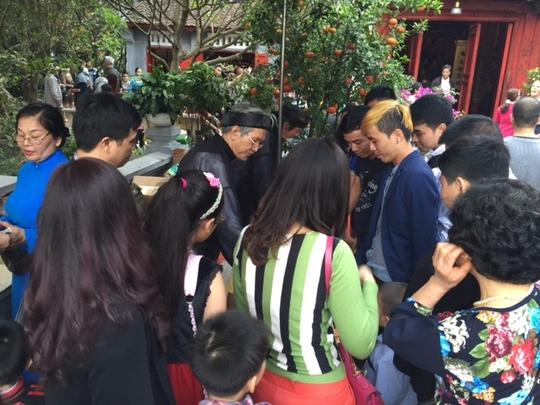 Hai ông đồ tại đền Ngọc Sơn tặng chữ cho khách tham quan. Rất nhiều người muốn xin chữ treo trong nhà nhân dịp năm mới