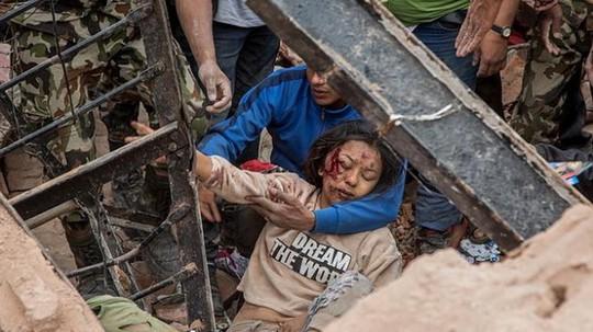 Một phụ nữ sống sót được cứu sống từ đống đổ nát ở thị trấn Dharara - Ảnh: Reuters