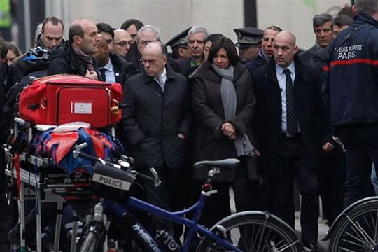 Bộ trưởng Nội vụ Pháp Bernard Cazeneuve (bìa trái) và Thị trưởng Paris, bà Anne Hidalgo tại hiện trường. Ảnh: AP