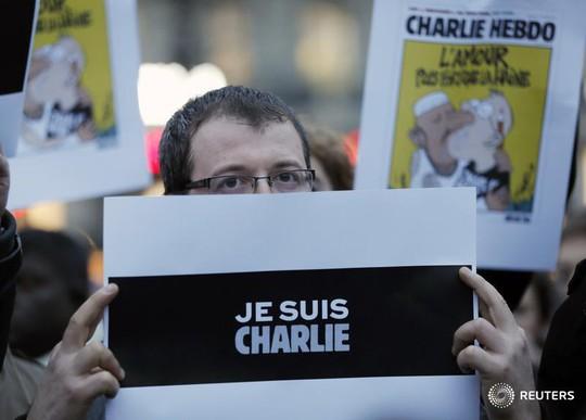 Hàng ngàn người Paris tuần hành thể hiện tình đoàn kết ngay sau vụ tấn công. Họ mang khẩu hiệu Je suis Charlie (Tôi là Charlie) để chia sẻ với tờ báo. Ảnh: REUTERS