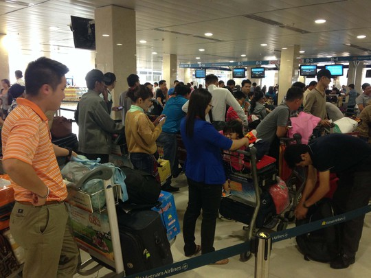 Hành khách chờ làm thủ tục ở sân bay quốc tế Tân Sơn Nhất sáng 13-2