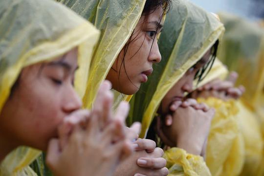 Các tín đồ cầu nguyện dưới mưa. Ảnh: ABS-CBN