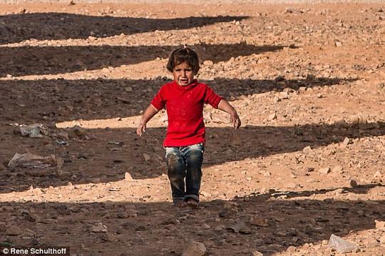 Cô bé đi chân trần trên nền đất đá. Ảnh: Daily Mail