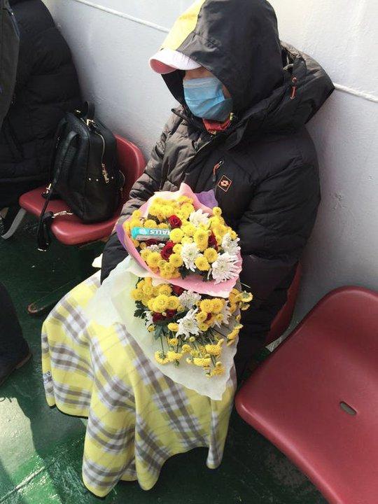 Một số người mang theo hoa để tưởng nhớ người thân thiệt mạng trong vụ chìm phà. Ảnh: CNA