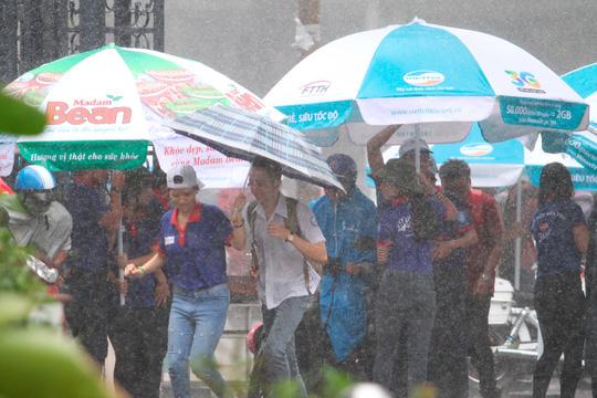 Sinh viên tình nguyện tại Trường ĐH Sư phạm TP HCM chịu ướt để đưa thí sinh vào điểm thi trong trời mưa tầm tã chiều ngày 1-7 Ảnh: Hoàng Triều